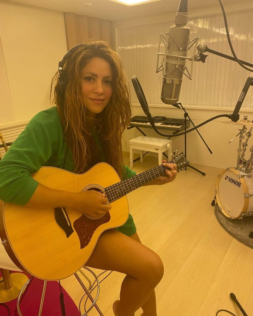 Shakira is in the studio with a guitar